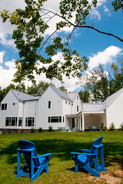 board and batten siding Exterior Farmhouse with Adirondack chairs blue patio